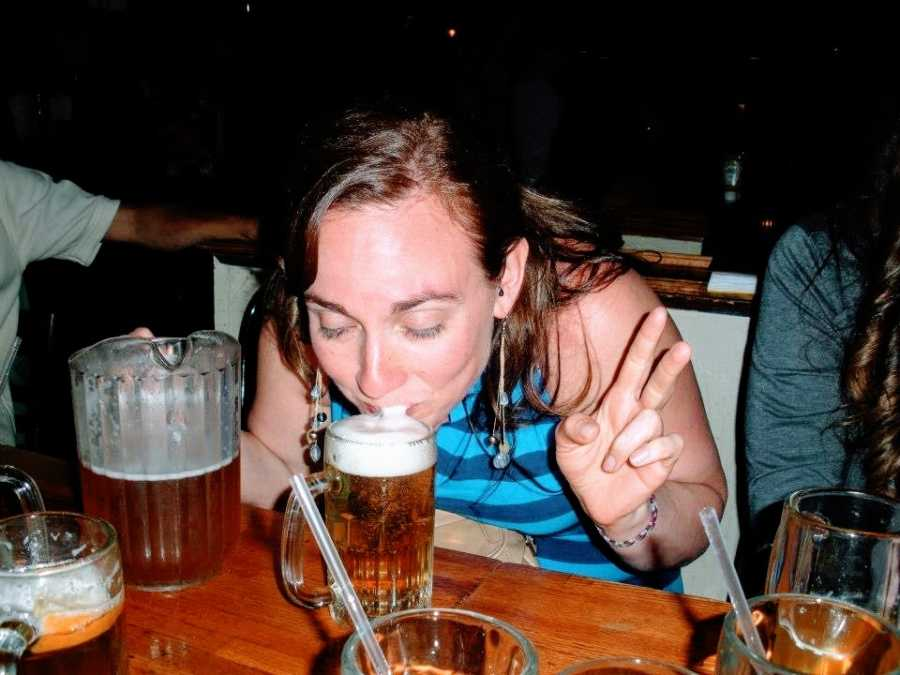 A woman drinks beer while holding up a peace sign