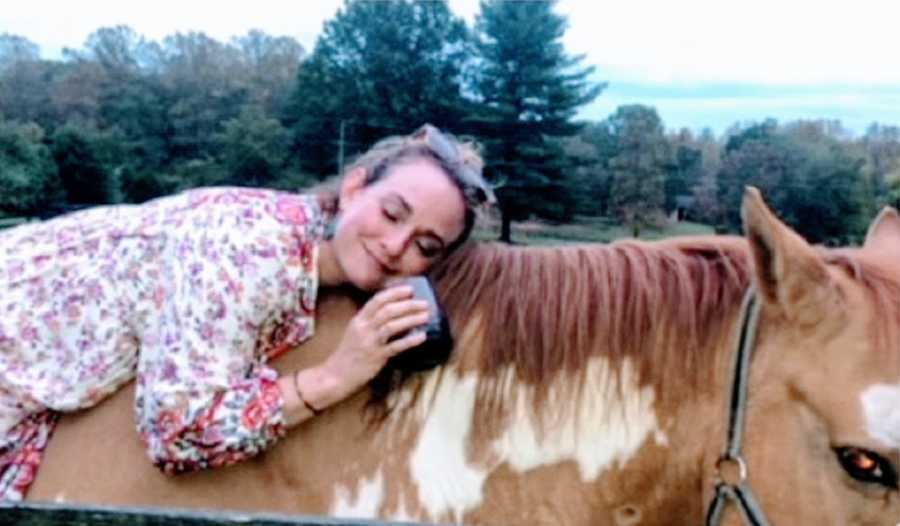 A drunk woman lays on top of a horse holding a bottle of alcohol