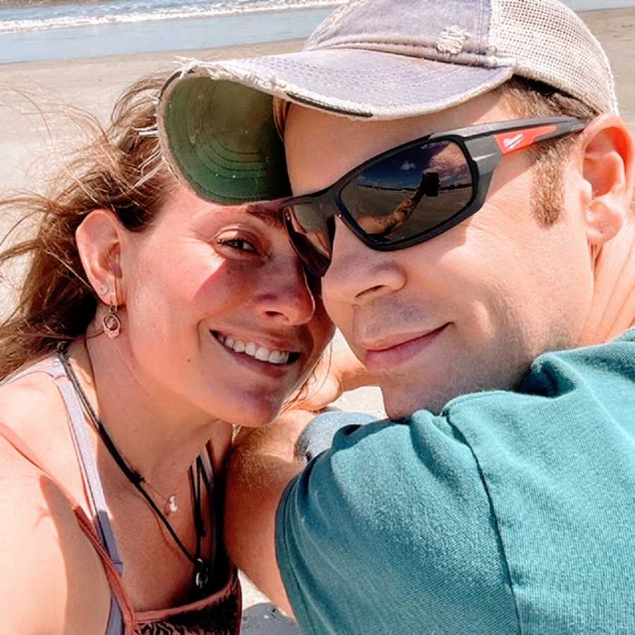 A woman and her husband sit together on a beach