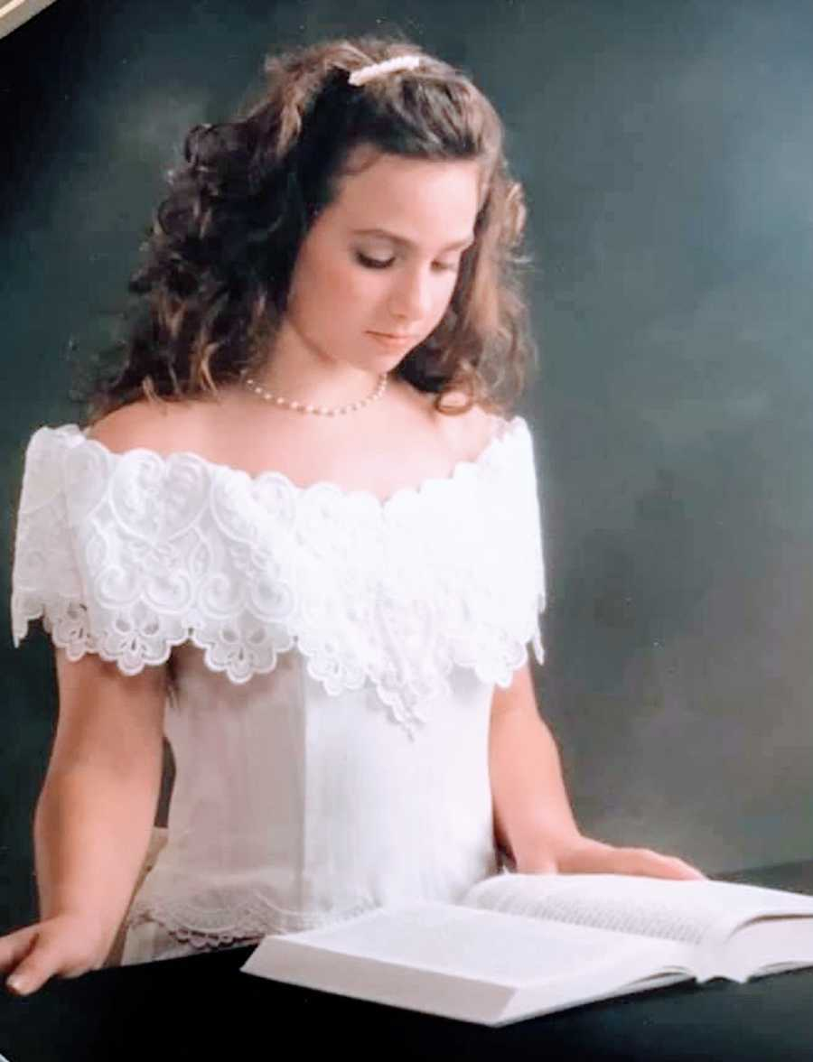A young woman in a white dress stands next to an open book