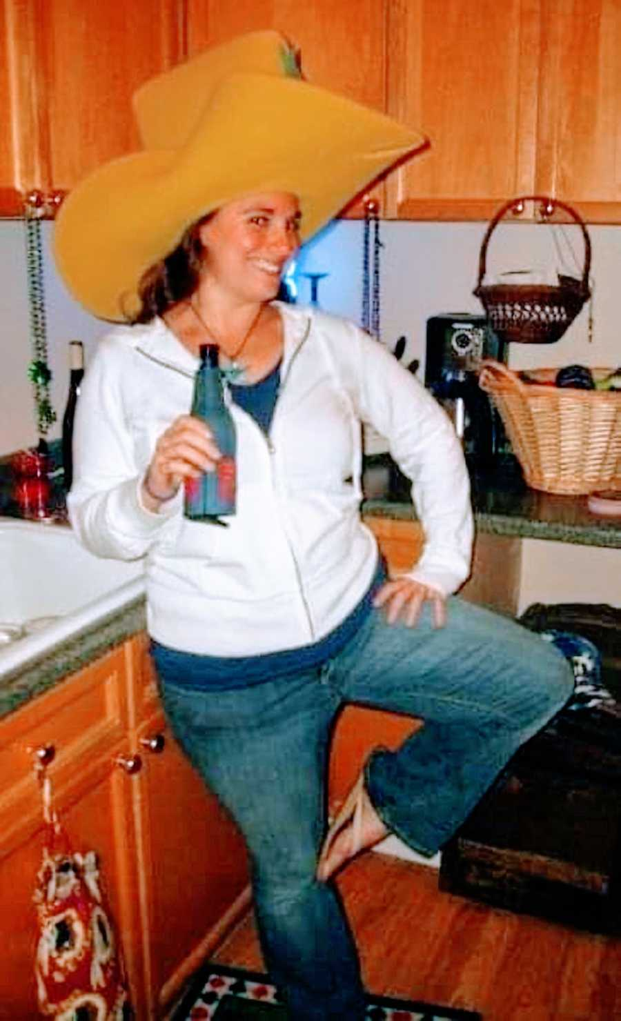 A woman wearing a giant cowboy hat stands on one foot while holding a beer
