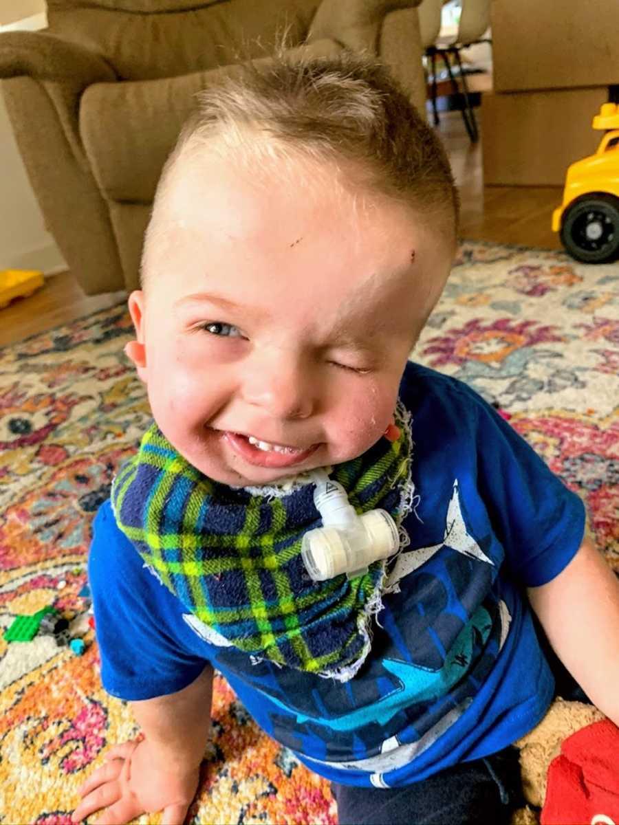 Baby boy wearing blue shirt smiling at camera