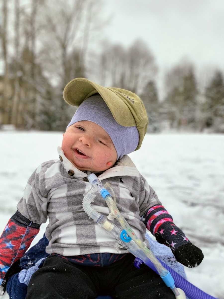 Baby boy wearing hat and smiling sitting outside in snow