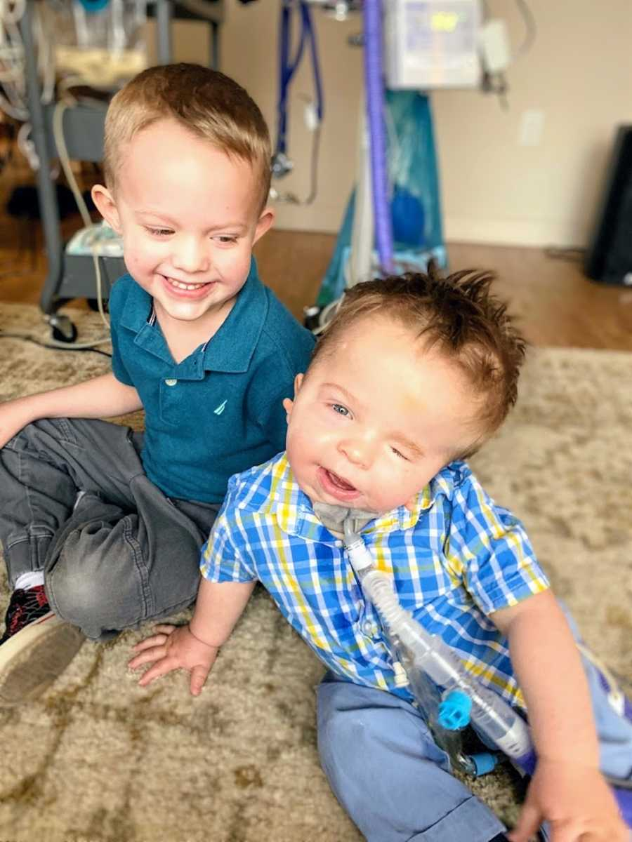 Brothers sitting on floor wearing blue