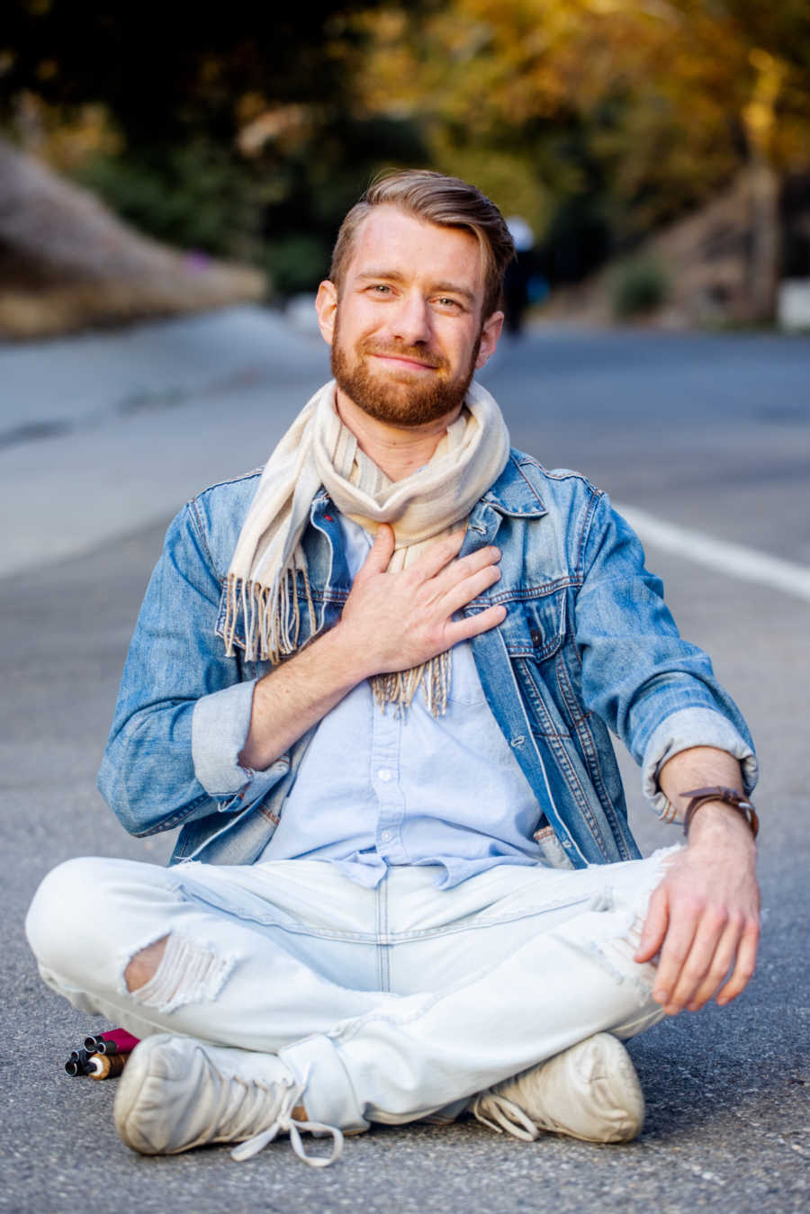 Man sitting cross-legged in the road with hand on heart smiling