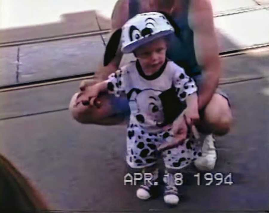 Young boy standing with mother wearing Disney's 101 Dalmations outfit
