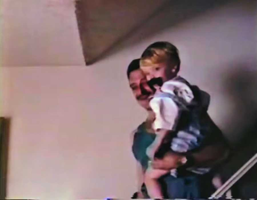 Father holding son on staircase, the son is wearing a fake moustache