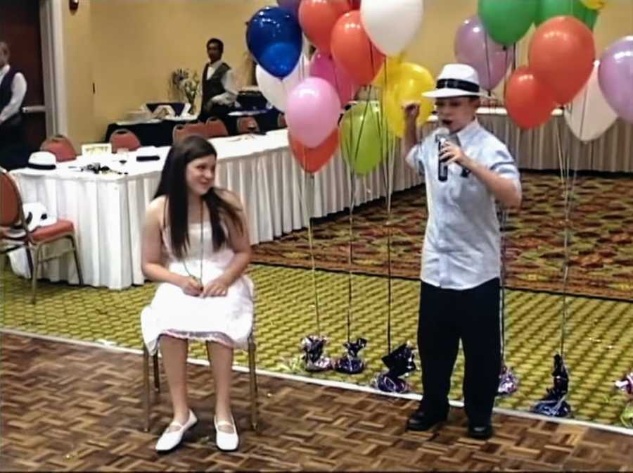 Girl sitting in a chair at birthday party and young boy standing next to her holding a microphone