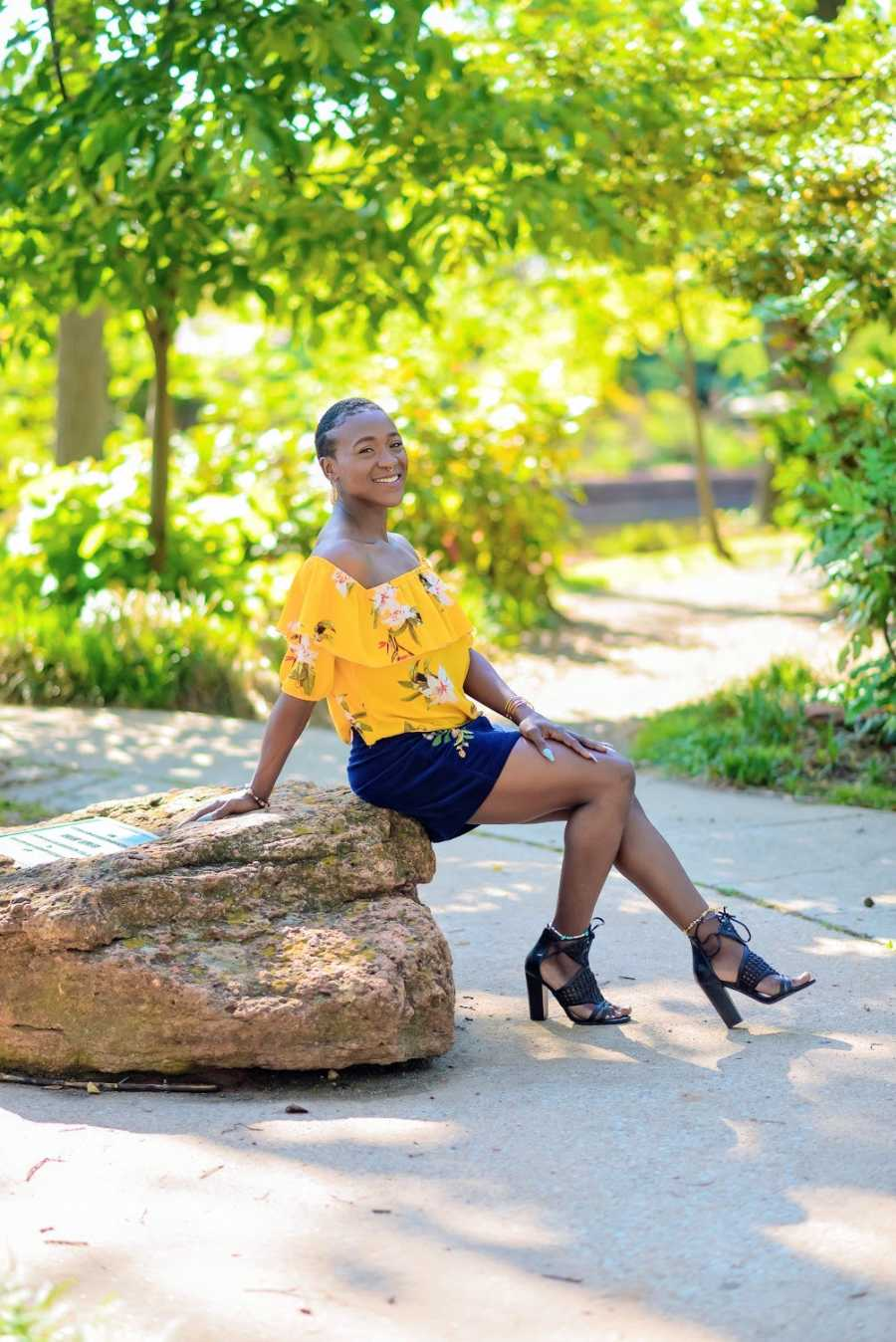 A woman wearing yellow sits on a rock in the park