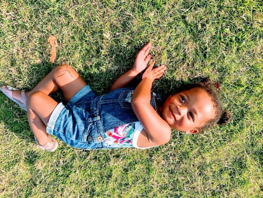 A little girl lies on her side in the grass