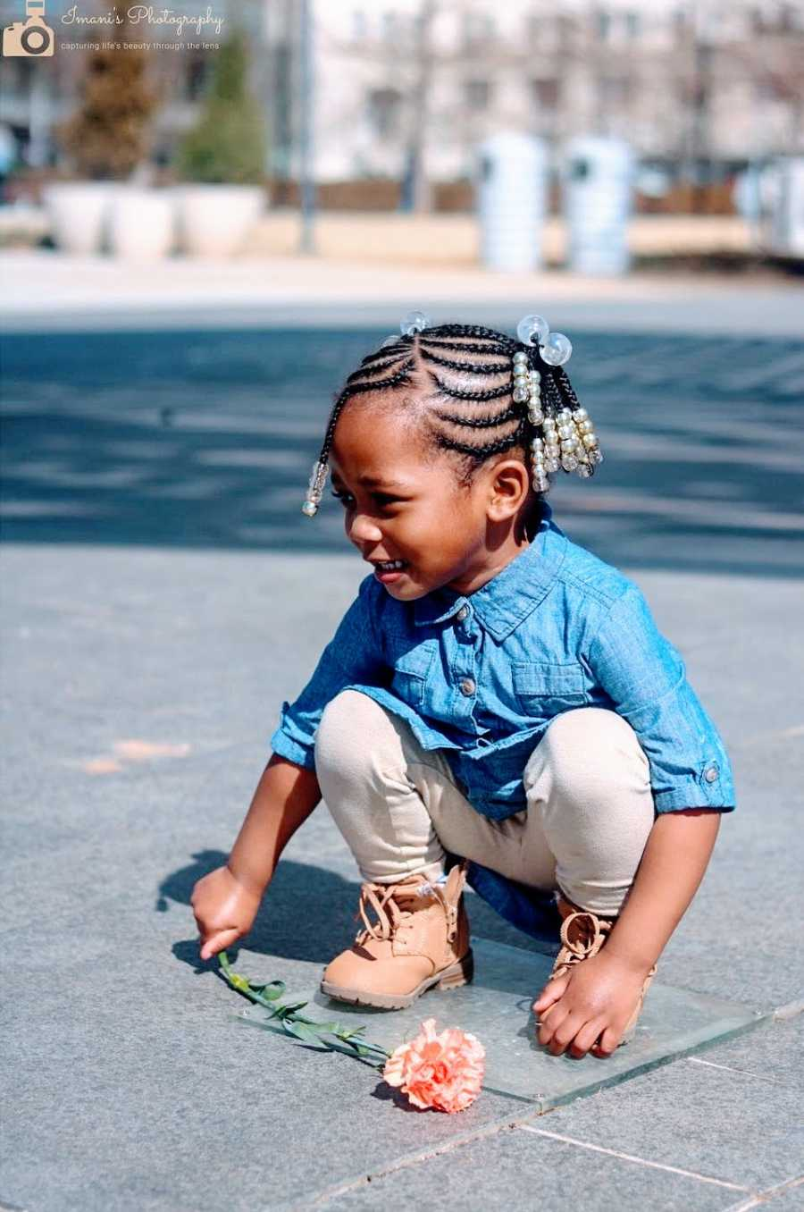 A little girl squats down holding a flower in her hand