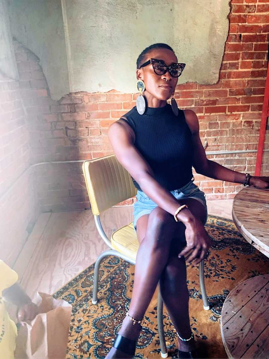 A Black woman sits in a chair wearing sunglasses and large earrings