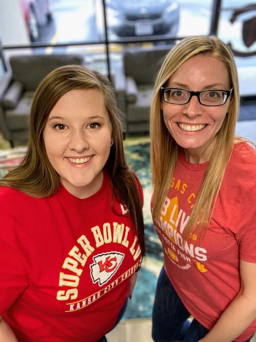 Two women wearing Kansas City football shirts smiling