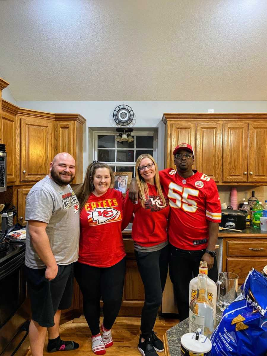 Four parents taking picture in kitchen