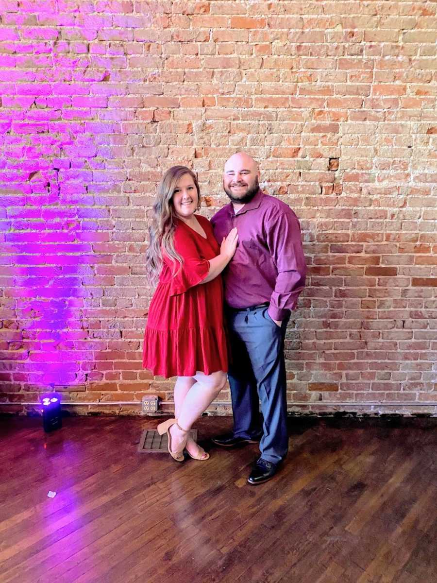 Couple standing and smiling in front of brick wall