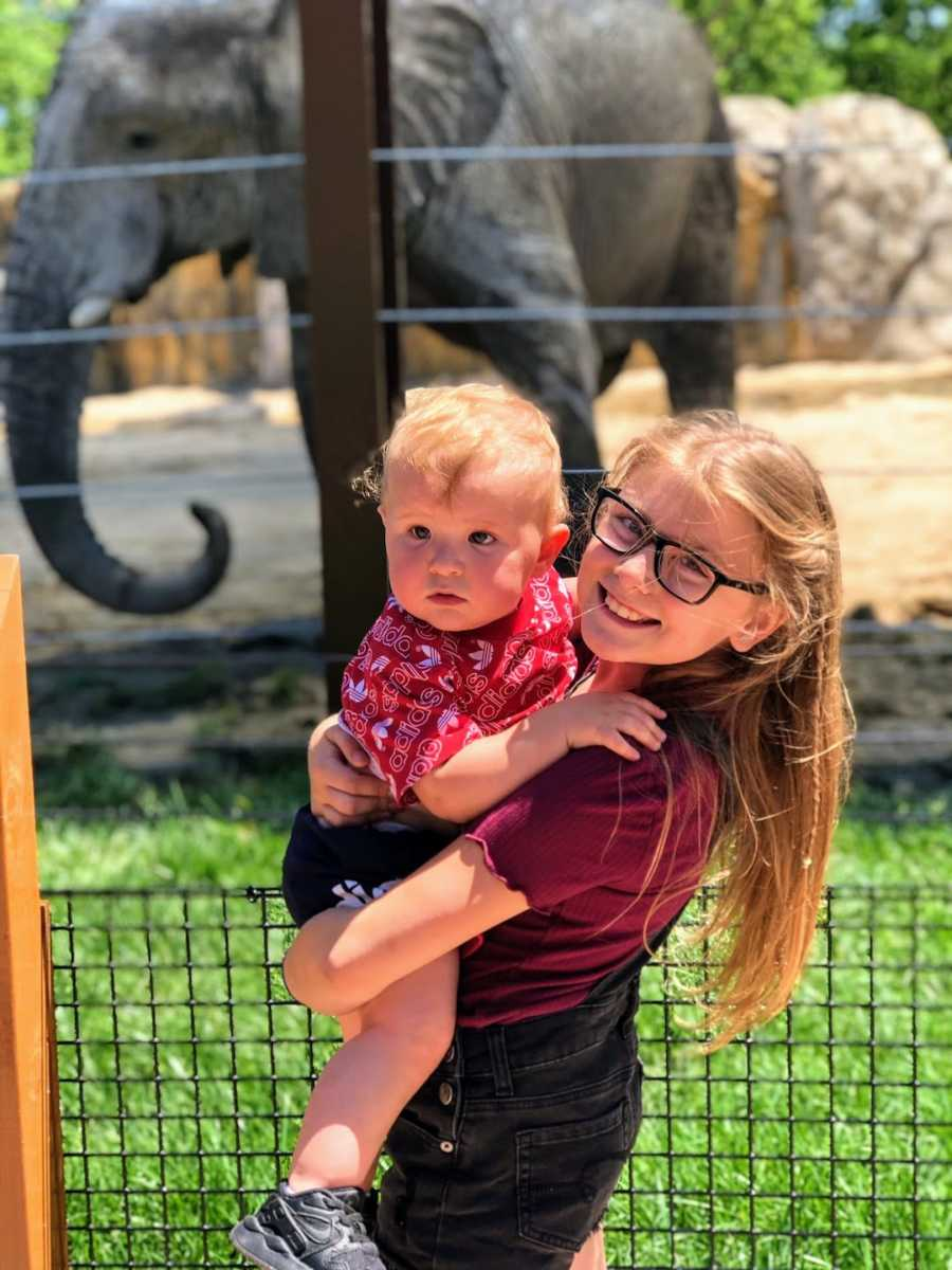 Sister holding baby sibling standing in front of elephant enclosure at zoo