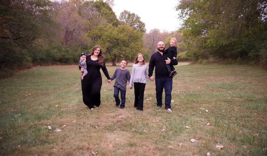 Family of six wearing black walking toward the camera outside