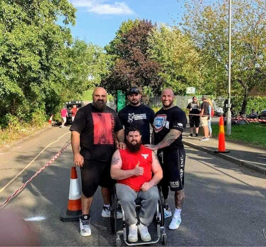Three men standing behind man in wheelchair doing thumbs-up