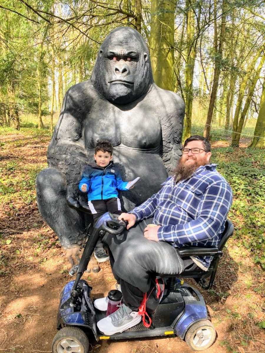 Man in wheelchair posing with son in front of gorilla statue