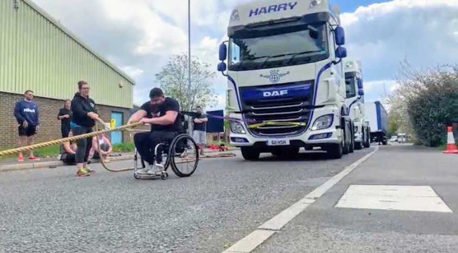Man in wheelchair pulling bus with rope at Strongman competition