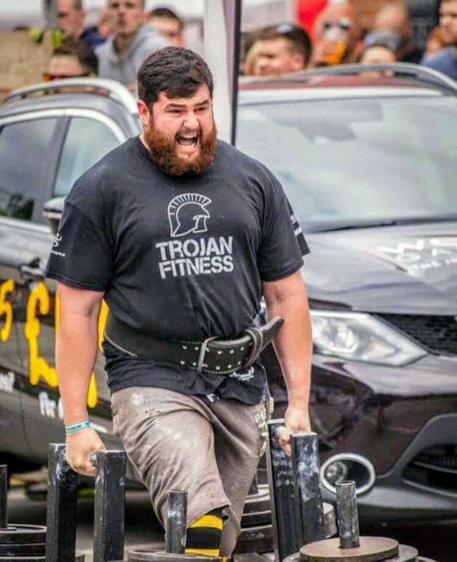 Man at fitness competition holding weights and walking
