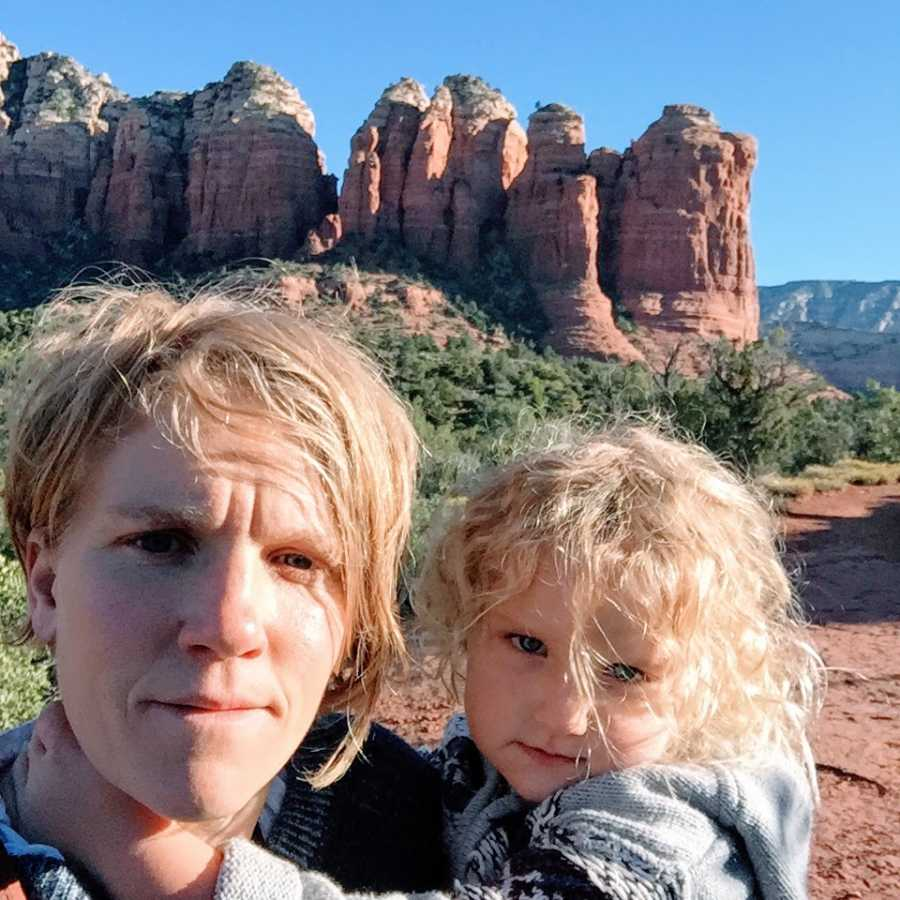 An autistic mother and holds her son in front of a desert landscape
