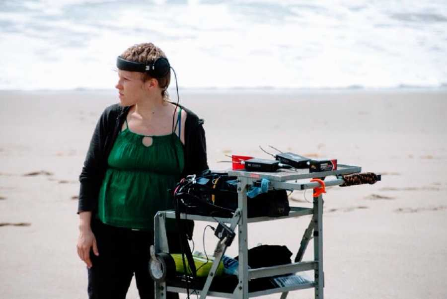 An autistic woman stands next to film sound mixing equipment