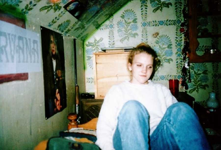 A young woman with undiagnosed autism sits in a wallpapered room