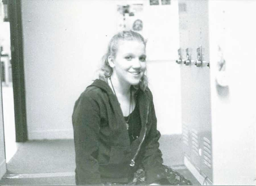 A young woman sits in a locker room alone