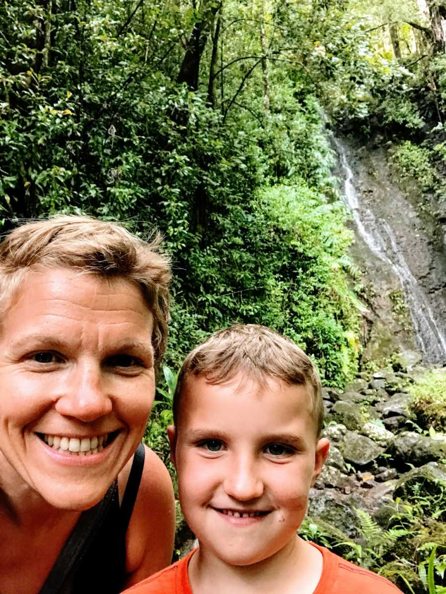 An autistic mom and her son in the woods by a waterfall
