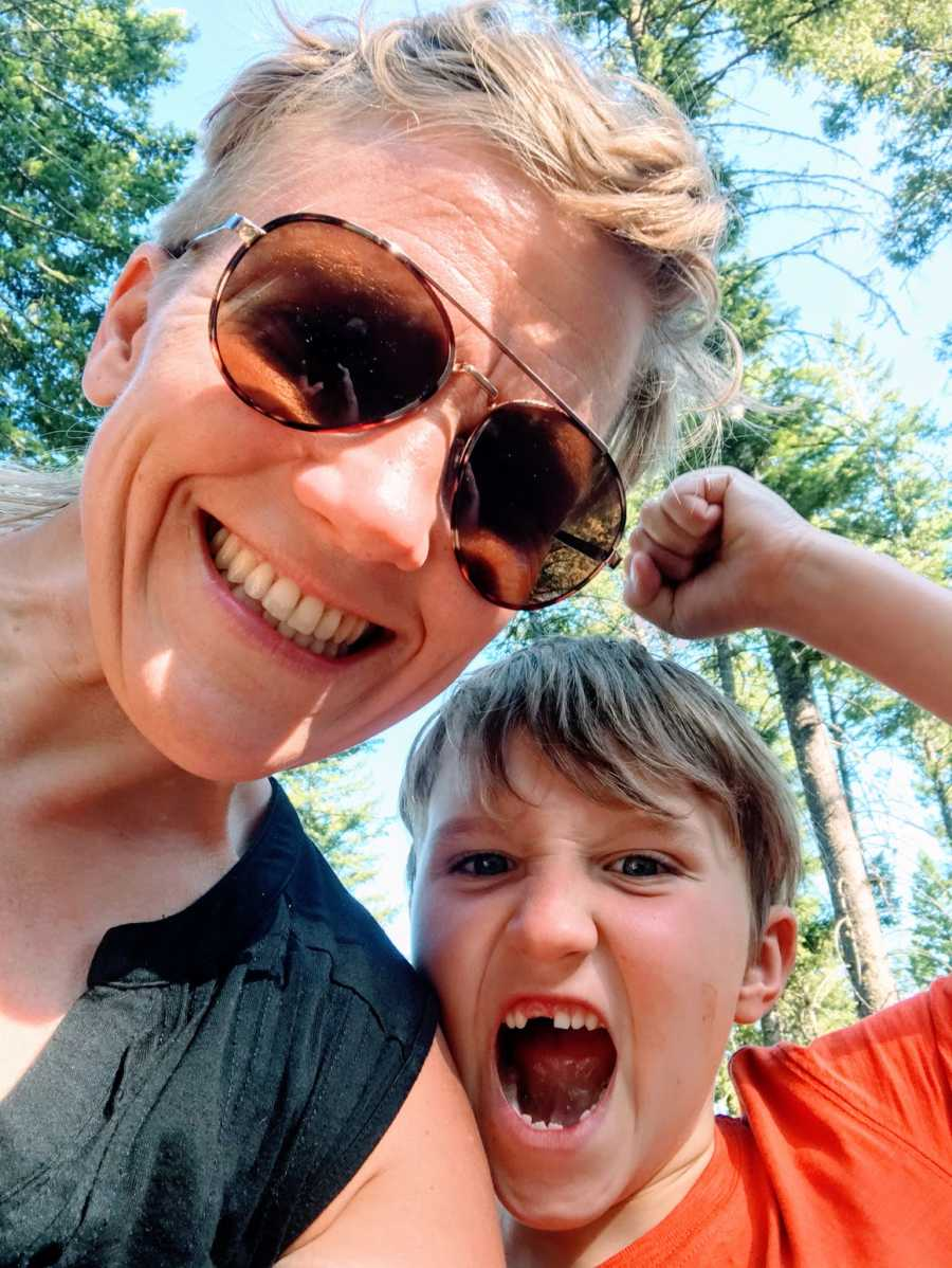 A mom in the woods with her autistic son, whose mouth is open