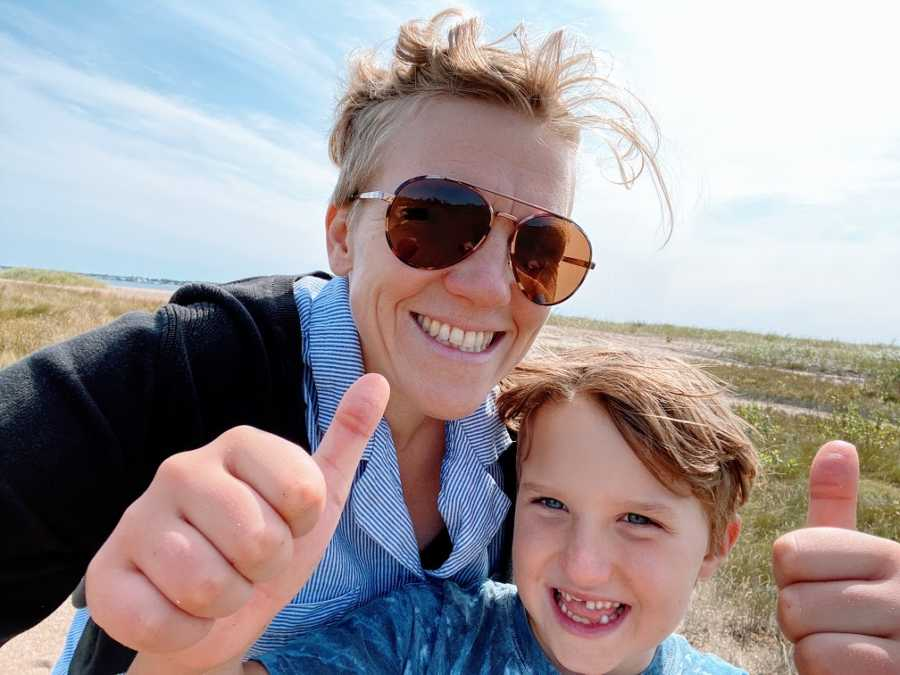 An autistic boy gives thumbs up to the camera while his mom smiles