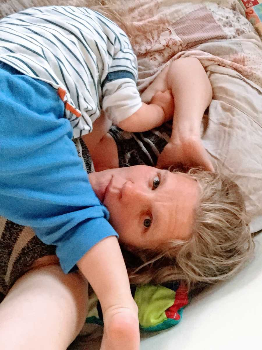 An autistic boy climbs on his mother who is lying down