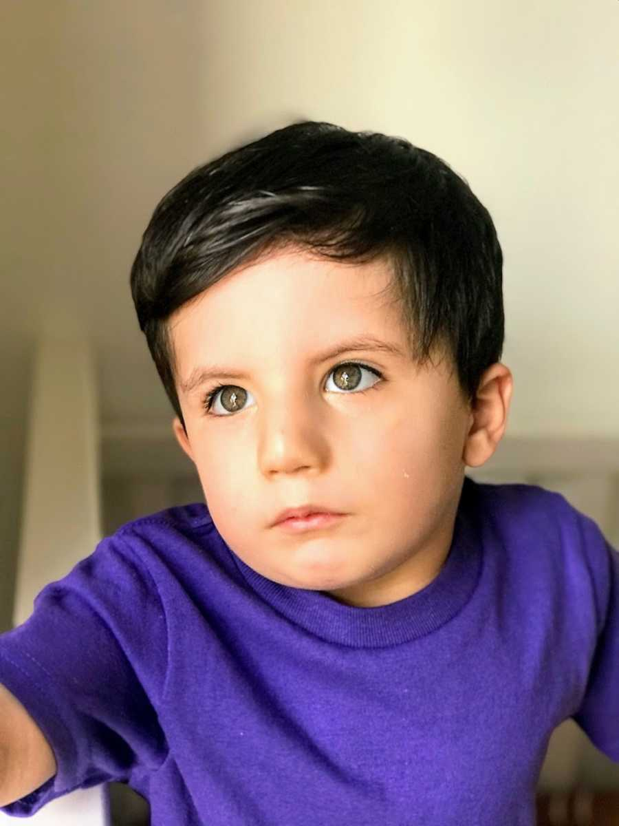 Toddler boy wearing purple shirt looking off into distance