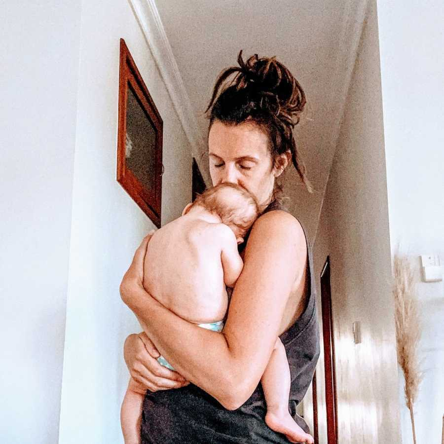 A mother holds her baby while standing with messy hair