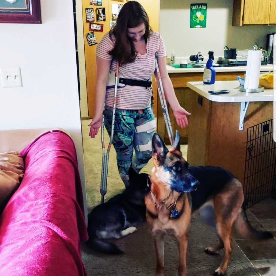 Woman standing with dogs using crutches