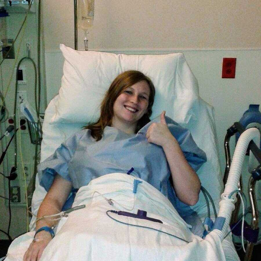 Young woman in hospital bed after surgery giving thumbs up