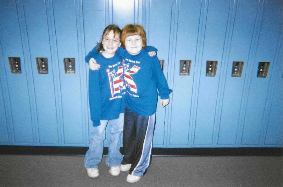 Old photo of two young girls wearing matching sweatshirts standing in front of blue lockers