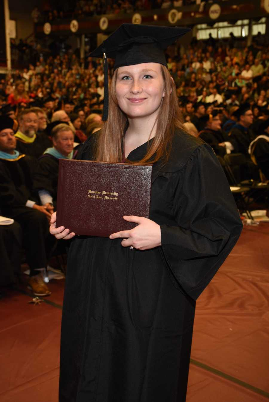 College graduate wearing cap and gown and holding diploma at graduation