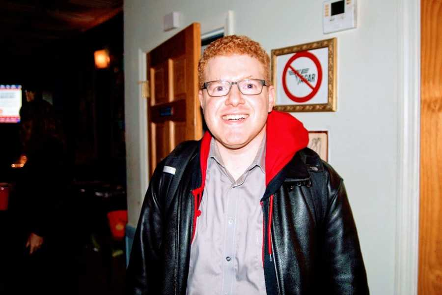 A comedian with red hair and glasses wearing a black leather jacket