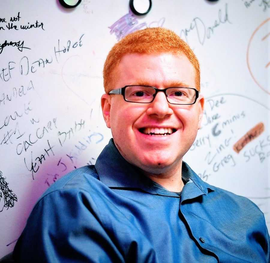A comedian stands in front of a whiteboard with writing on it