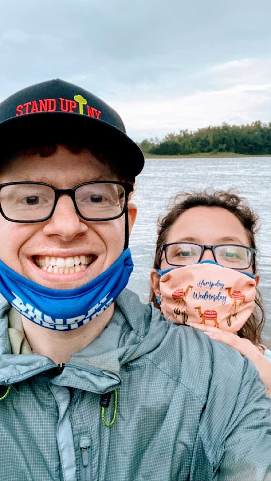A comedian and his wife in masks by the water