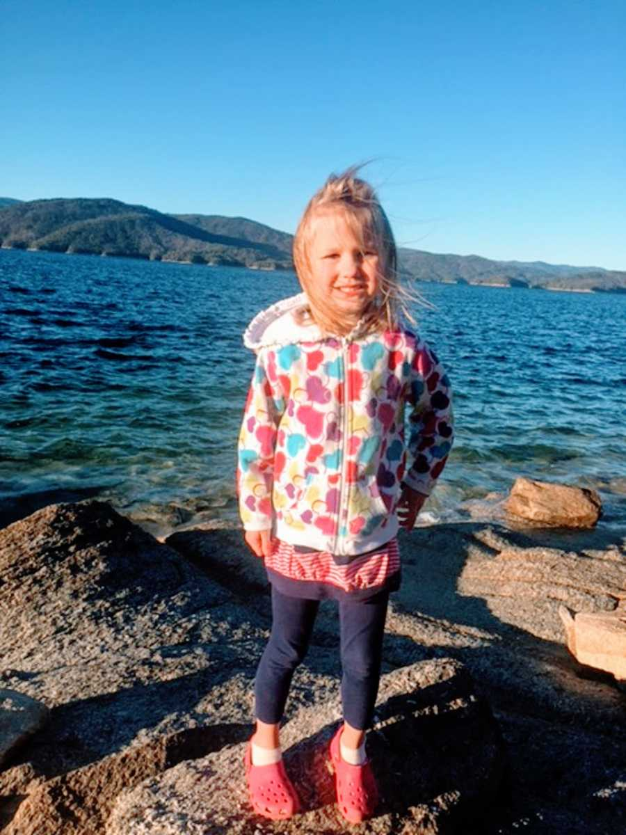 A young adopted girl stands on rocks by the water