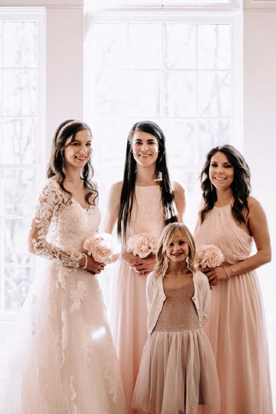A bride and her sisters stand together wearing dresses