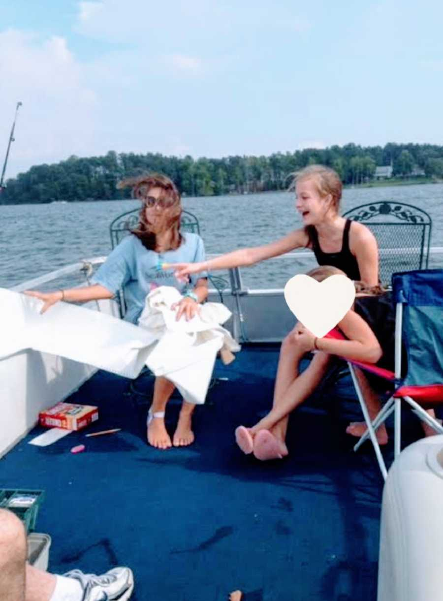 Three young women sit together on a boat