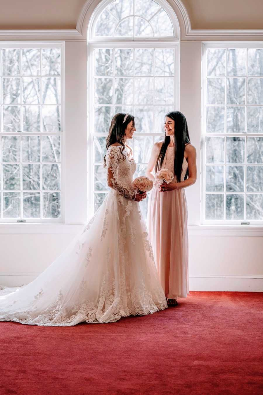 A woman and her adopted sister stand together at her wedding
