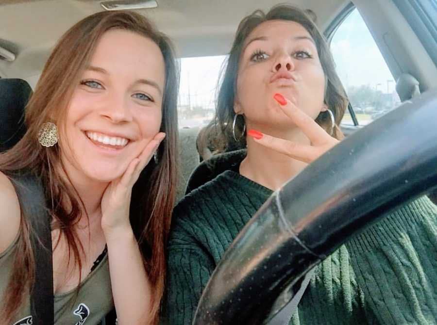 A young woman and her sister making fun faces in a car