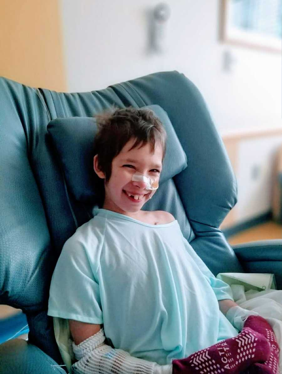 A boy with a rare chromosome disorder smiling and sitting in a chair at a hospital