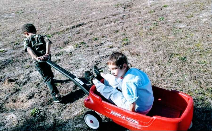 A boy with a rare chromosome disorder is pulled by his brother in a wagon