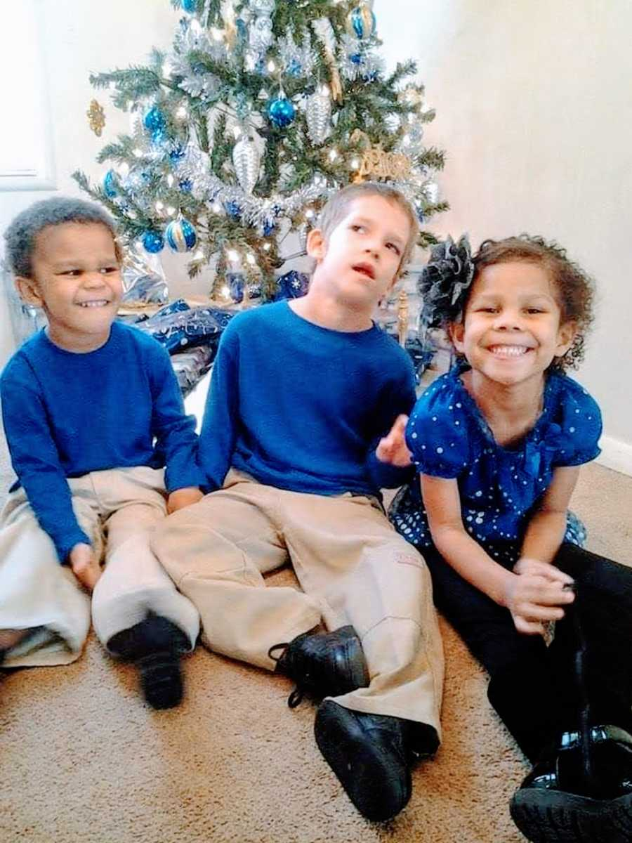 A boy with a rare chromosome disorder sits next to his siblings at Christmas